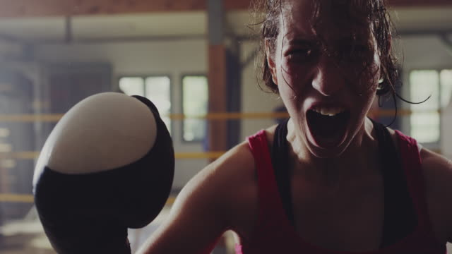 Female boxer screaming in boxing ring after won a match video