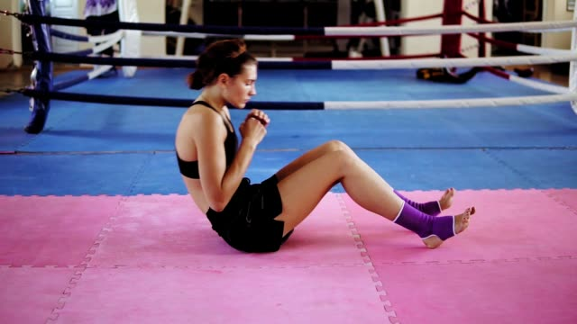 Female boxer training in a gym: athletic young woman doing abdominal crunches inside of the boxing ring in gym video