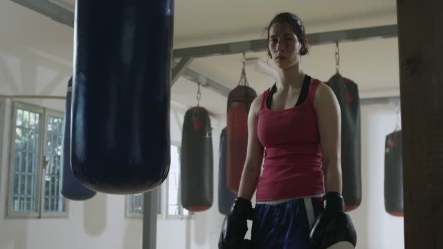 female boxer training with a punching bag - irriducibilità video stock e b–roll
