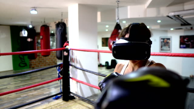Female boxer training with Virtual reality headset - video game
