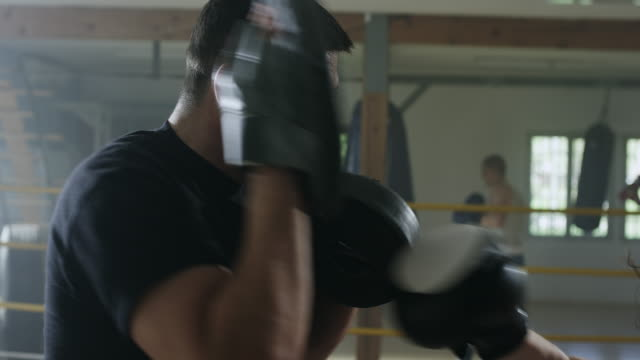 a female boxer working with a trainer at boxing gym - sparring allenamento video stock e b–roll