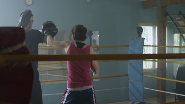 A female boxer working with a trainer at boxing gym video