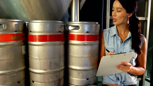 Female brewer maintaining record on clipboard 4k - video