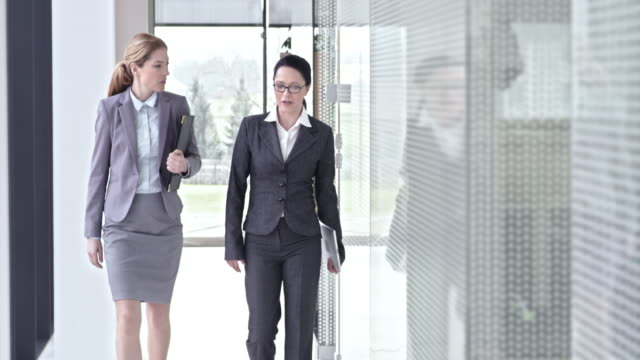 SLO MO Female business colleagues talking and walking in hallway video