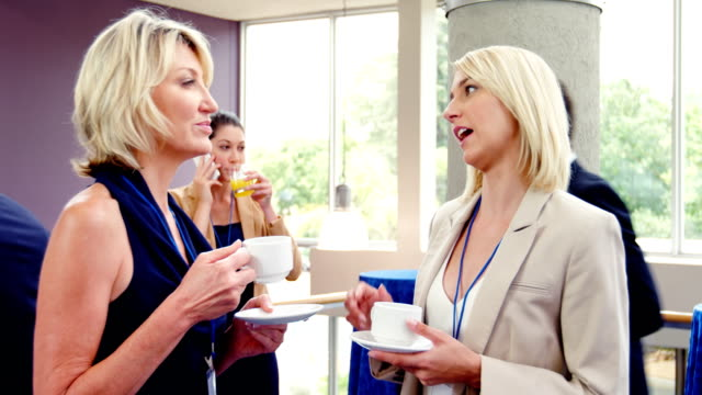 Female business executives interacting with each other while having coffee Female business executives interacting with each other while having coffee at conference center coffee break stock videos & royalty-free footage