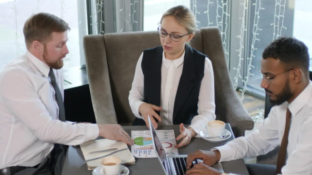 Female Business Leader Discussing Project with Diverse Male Colleagues in Cafe