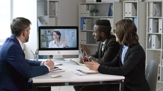 Female Business Leader Web Conferencing with Team Young beautiful businesswoman waving and talking to diverse business team from computer screen during web conference in the office online meeting stock videos & royalty-free footage