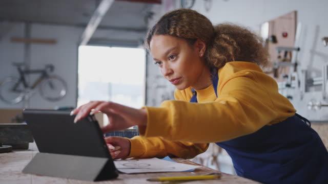 kvinnliga företagare i verkstad för att bygga cyklar med digital surfplatta - småföretagande bildbanksvideor och videomaterial från bakom kulisserna