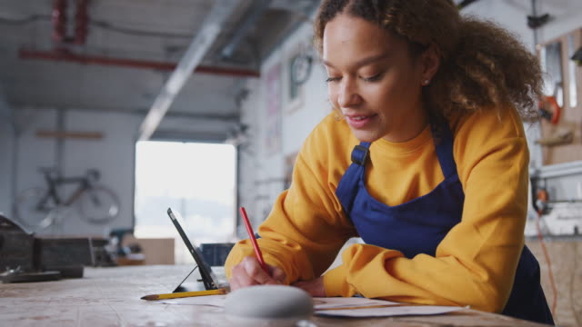 Female Business Owner In Workshop Working On Drawing And Asking Smart Speaker Question