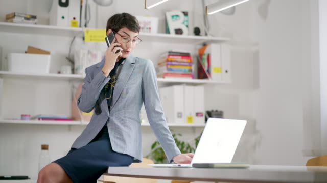 female business owner leaning on a desk in the office while talking on the phone - owner laptop smartphone video stock e b–roll