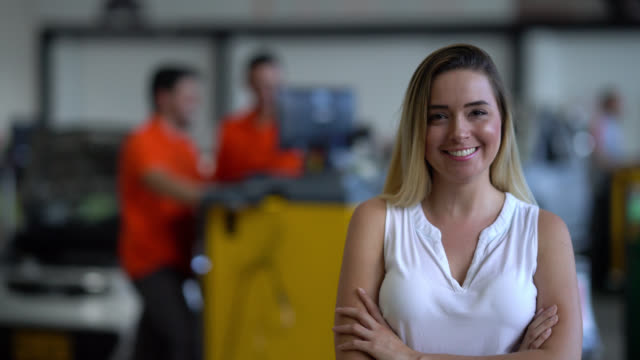 Female business owner of an auto repair shop looking at the camera smiling video