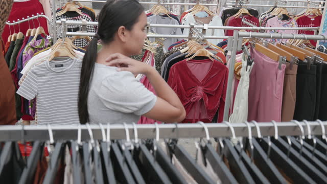 Female business owner or designer of Asian descent aged 30-40 years starting up a clothing store. In the market at night