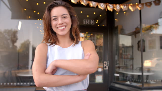 Female business owner outside cafe walking into focal plane