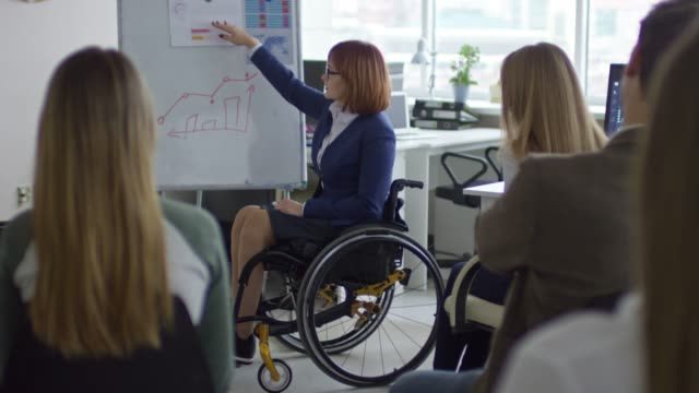 female business trainer in wheelchair speaking to employees - direttrice video stock e b–roll