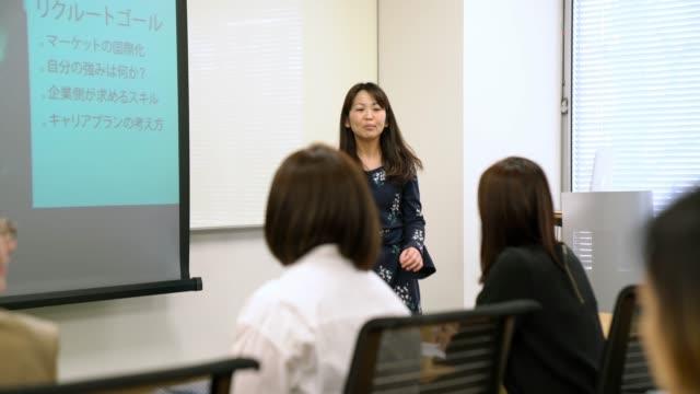 vidéos et rushes de femme d'affaires femme donnant une présentation - culture japonaise
