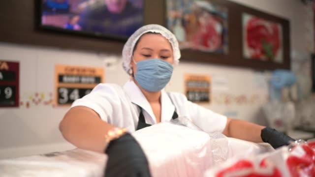 vídeos de stock e filmes b-roll de female butcher walking and working at butcher's shop - supermarket worker