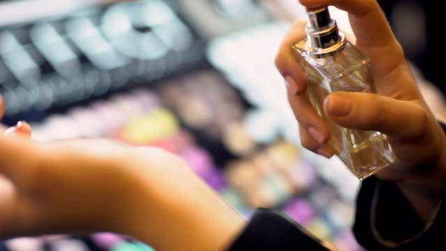 female buyer testing perfume ship, spraying fragrance on wrist, top aroma notes - makijaż filmów i materiałów b-roll