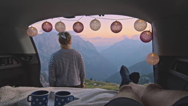 SLO MO Female camper enjoying the sunset in front of her partner
