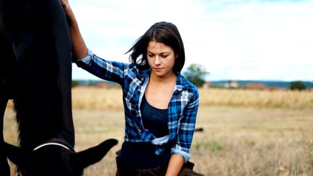 女性彼女の馬の世話 - 動物に乗る点の映像素材/bロール