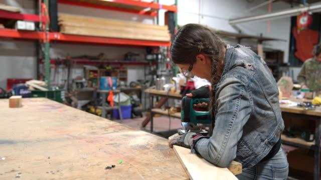 Female carpenter cutting wood in a workshop video