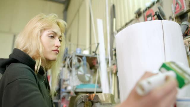 female carpenter painting tree stump in workshop - potere femminile video stock e b–roll