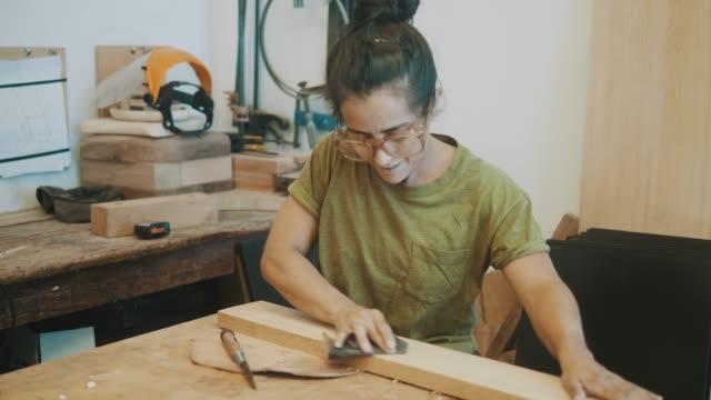 weiblicher tischler-sandpapier (zeitlupe) - tischlerarbeit stock-videos und b-roll-filmmaterial