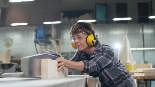 Female Carpenter Sawing Wood Medium shot of female joiner wearing safety headphones and goggles cutting piece of wood with electric jointer carpenter stock videos & royalty-free footage