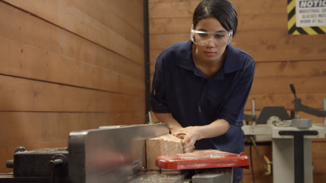 Female Carpenter Using Plane In Woodworking Woodshop - vídeo