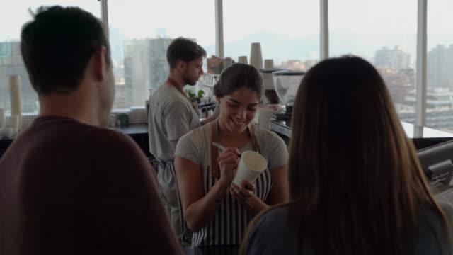 weibliche kassiererin, die eine kaffeetasse an den partner übergibt, nachdem sie eine nachricht darauf geschrieben hat - barista stock-videos und b-roll-filmmaterial