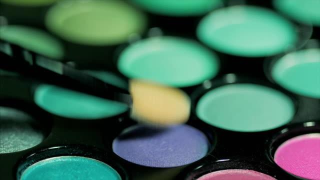 vídeos de stock e filmes b-roll de female caucasian hand is testing a violet and blue eyeshadow pallet - sombra para os olhos