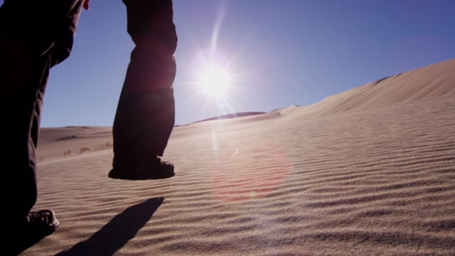 Female Caucasian hiker trekking across desert sand dunes Female climber desert traveller sun flare shadow adventure footprint hiker backpack success confident activity ambition arid RED EPIC mojave desert stock videos & royalty-free footage