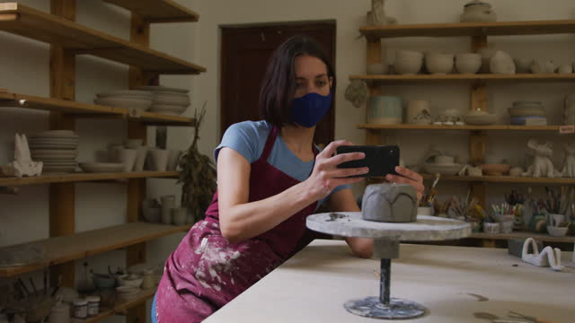 Female caucasian potter wearing face mask and apron taking picture of pot on potters wheel at potter