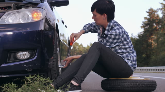 female changing a tire outdoors. video