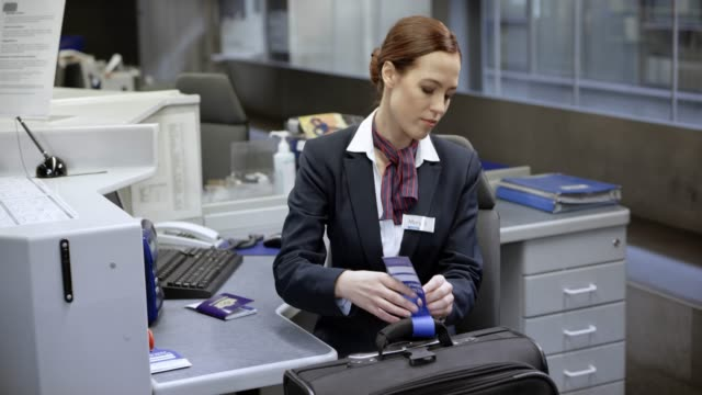 Female check-in staff putting a bag tag on the passenger's baggage and giving back the passenger's passport video