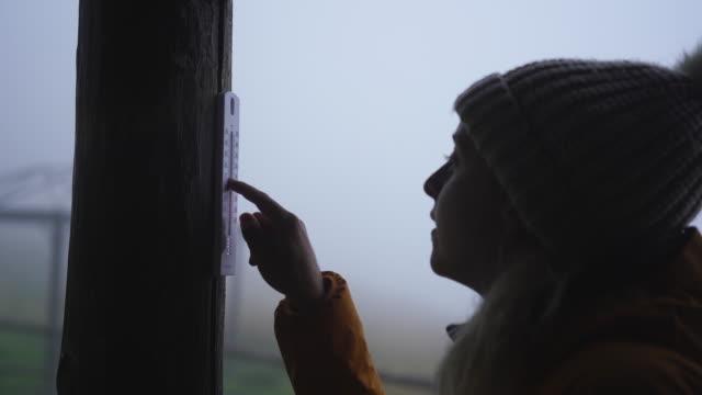 Female checks temperature on thermometer outside stone hut