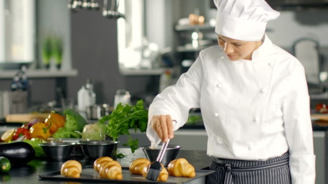 Female Chef  Baker Butters Croissants with Oil. video