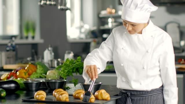 Femme Chef Baker Butters Croissants avec de l'huile. - Vidéo