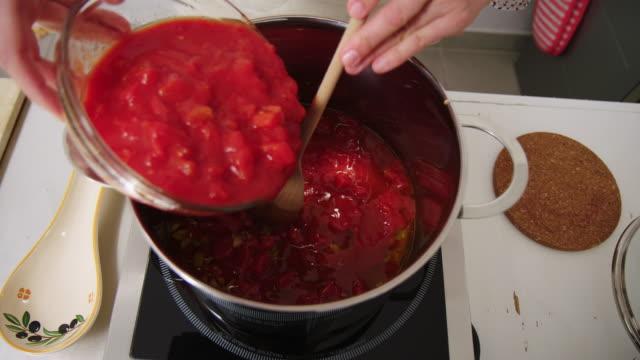 vídeos de stock e filmes b-roll de female chef cooking in kitchen - sauce tomatoes