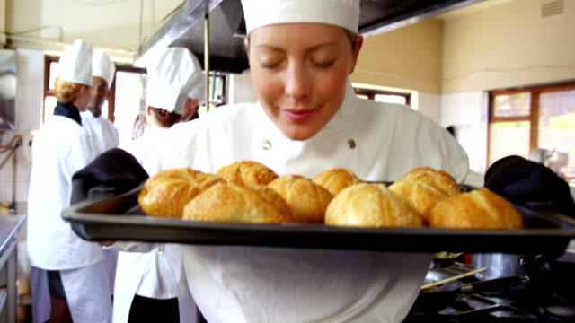 Female chef holding bun in cooling tray video