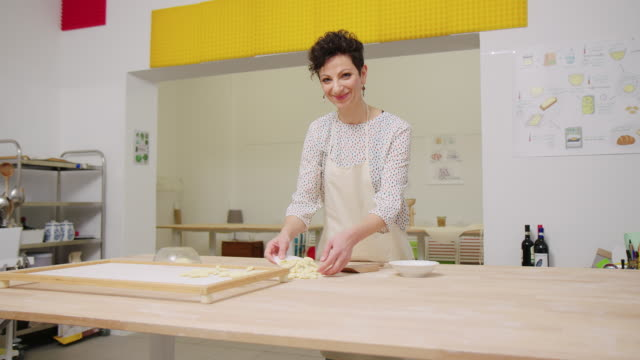 Female chef making preparing pasta at cooking class