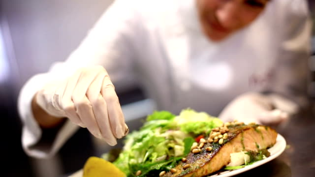 Female chef serving a meal. Blurry middle aged caucasian female chef placing parsley and seasoning on close-up of salmon steak dish.  She is wearing a white coat and white gloves when touching ready to eat food. commercial kitchen stock videos & royalty-free footage