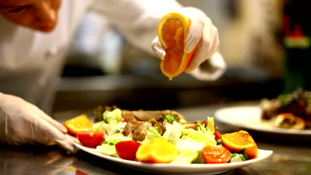 Female chef serving a meal. Adult female chef placing finishing touches on closeup of salad meal.It's classic salad with steak slices.Using protective gloves when touching ready to eat food.HD 1080. commercial kitchen stock videos & royalty-free footage