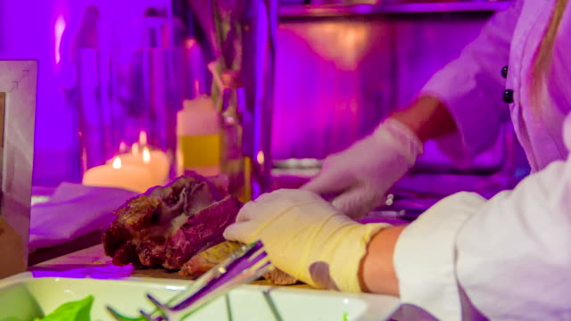 Female chef`s assistant carefully slicing roasted pork`s leg