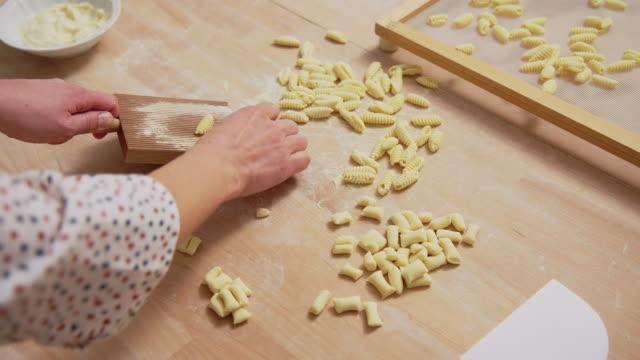 Female chef's hand making homemade pasta