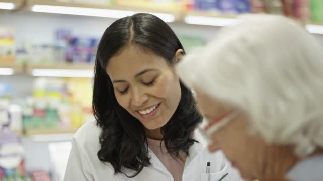 Female chemist talking to elderly woman in pharmacy Handheld shot of female chemist talking to elderly customer. Mid adult pharmacist is discussing with senior woman. They are standing at pharmacy. pharmacist stock videos & royalty-free footage