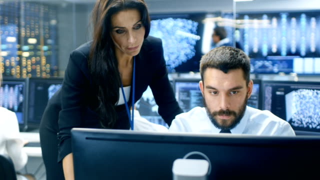 Female Chief Computer Engineer Consults Male Neural Network Architect. They Work in a Crowded Office on a Neural Network/ Artificial Intelligence Project. Office Space Has Data Server and Displays Showing Algorithms. video