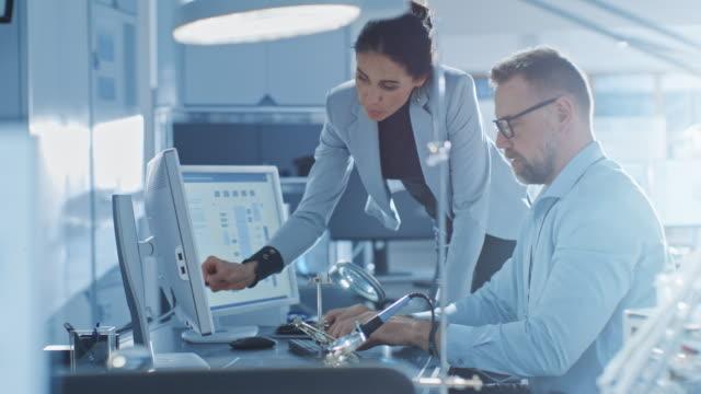 女性チーフエンジニアは、物事を説明し、男性の電子機器の専門家と話をし、彼はコンピュータ上で動作し、彼女と同意します。スタイリッシュな人とモダンで明るいオフィス - 研究所点の映像素材/bロール