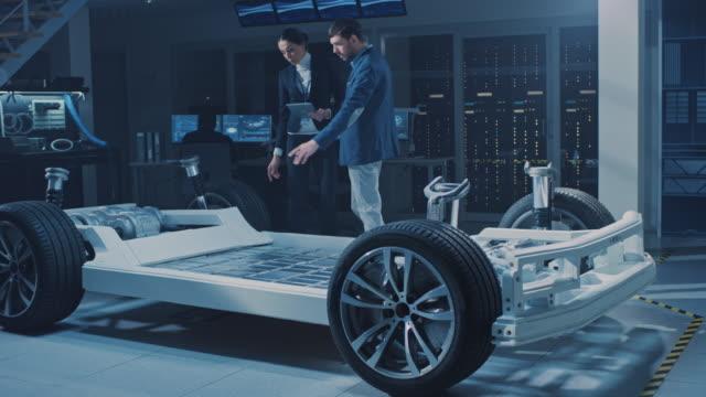女性チーフエンジニアがタブレットコンピュータを使用し、ハイブリッドエンジンの効率を説明し、重要な投資家に自律電気自動車のコンセプトを紹介します。車両シャーシは、ホイール、� - 自動運転車点の映像素材/bロール