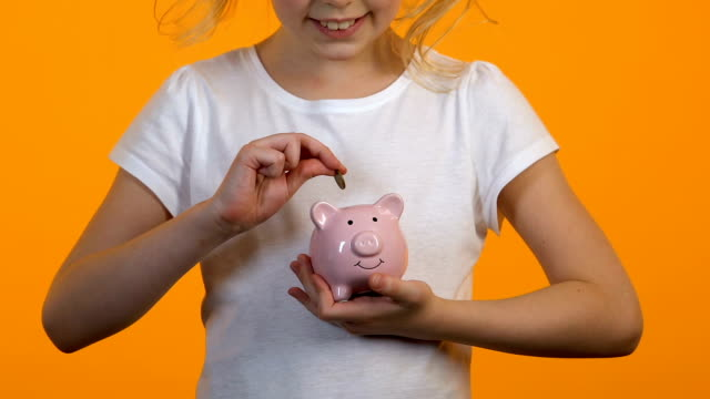 Female child putting coins into piggy bank, savings and personal budget, finance