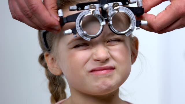 vidéos et rushes de enfant femelle louche des yeux utilisant le cadre optique d'essai, l'examen de oeil, la myopie - réfracteur